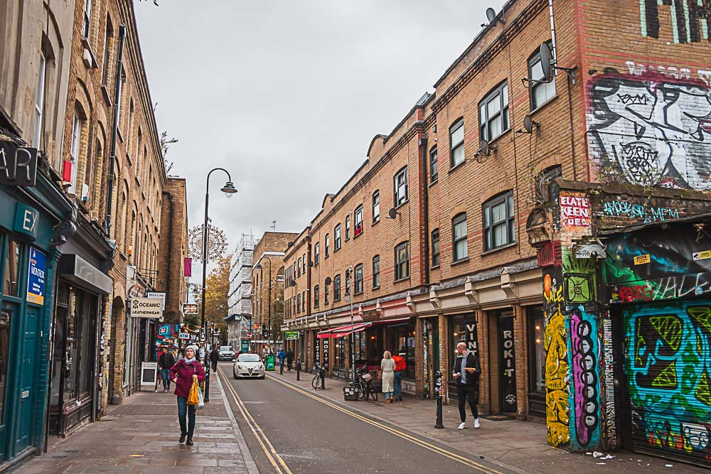 Brick Lane in London mit Street Art, Häusern und Restaurants